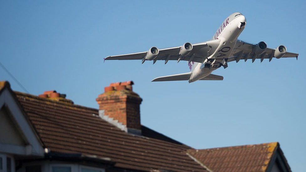 An aircraft flies over homes in Feltham after taking off from Heathrow Airport