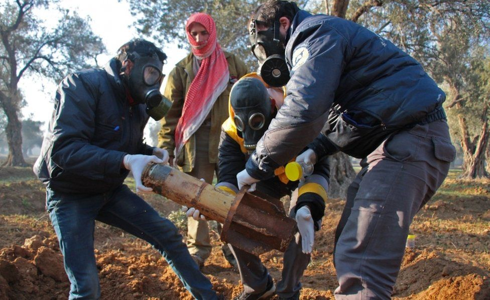 Syria Civil Defence members in gas masks carefully handle remnants of a rocket