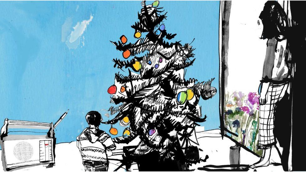 Tom as a boy stood by the Christmas Tree with his mum looking on
