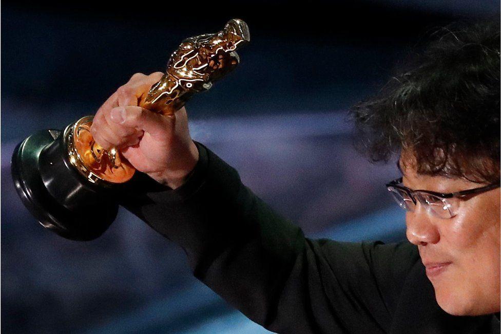 Director Bong Joon Ho holds his Oscar aloft