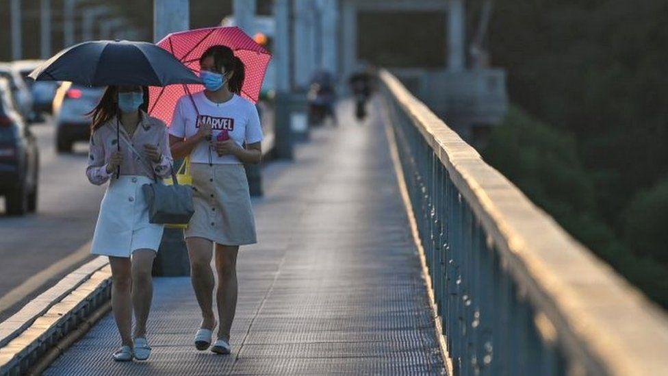 Women walking across bridge in Wuhan city