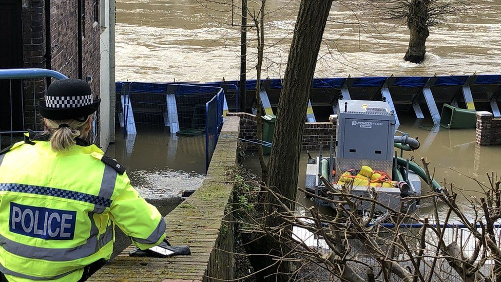 Temporary flood barriers which have been moved by the River Severn towards the Wharfage in Ironbridge, Shropshire.