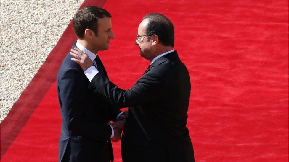French outgoing President Francois Hollande (R) is escorted by his successor Emmanuel Macron as he leaves the Elysee presidential Palace at the end of their handover ceremony and prior to Macron's formal inauguration as French President on 14 May 2017 in Paris