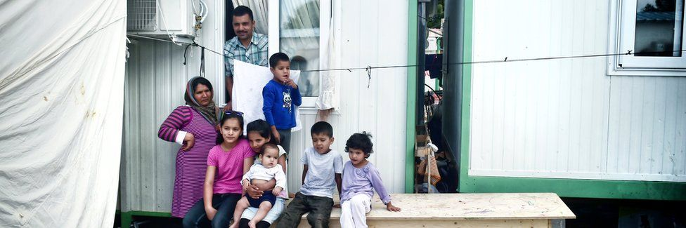 An Afghan family with six children stand outside their container on 11 May 2017 at Malakassa refugee camp in Greece
