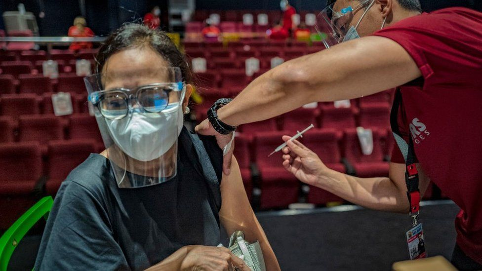 A healthcare worker administers a dose of Sinovac Biotech's CoronaVac vaccine to a woman at a mall theatre converted into a vaccination centre on June 1, 2021 in San Juan, Metro Manila, Philippines