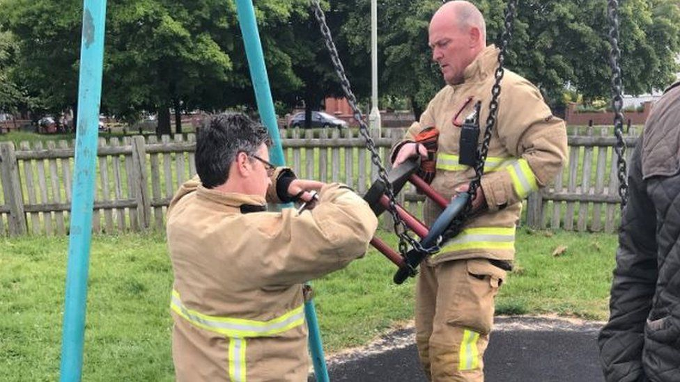 Firefighters putting swing back together