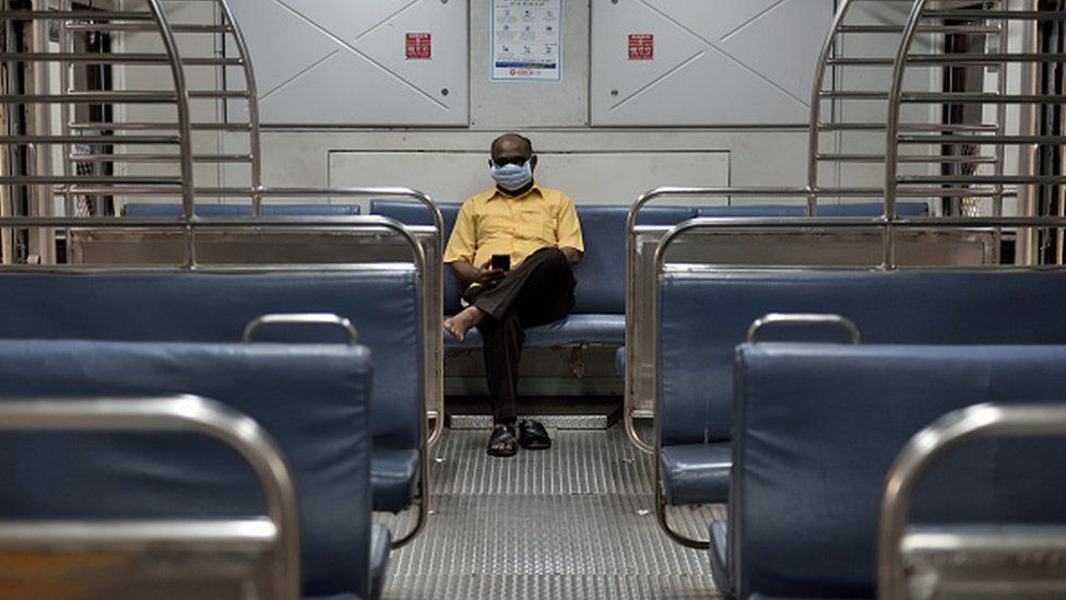 A passenger is seen wearing a protective mask as a precaution from coronavirus in the local train at CST railway station, on March 14, 2020 in Mumbai, India.