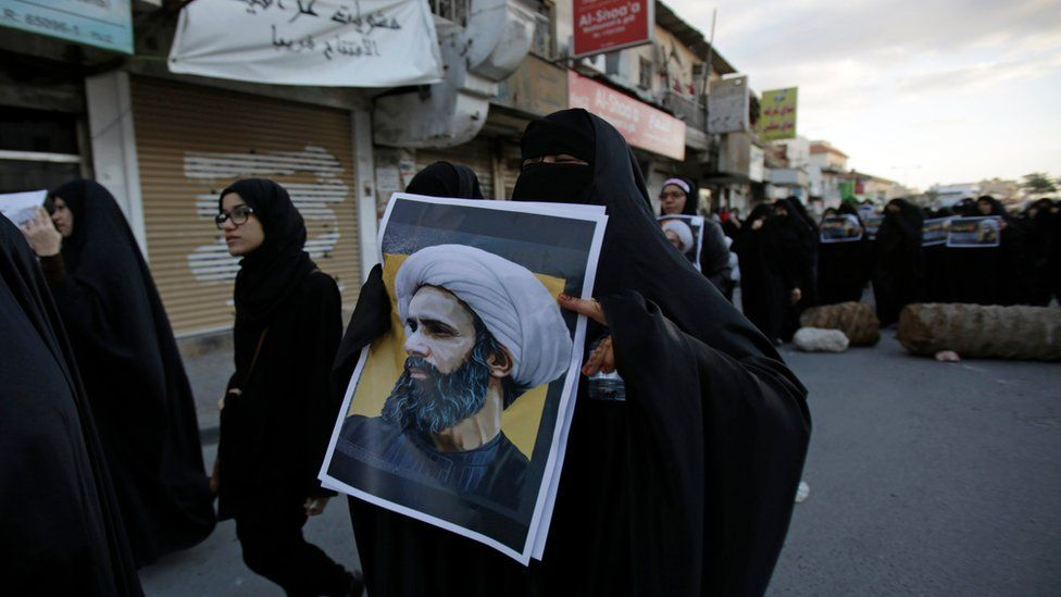 A Bahraini protester holds a picture of Saudi Shiite cleric Sheikh Nimr al-Nimr during a rally denouncing his execution by Saudi Arabia, Sunday, Jan. 3, 2016, in Daih, Bahrain.