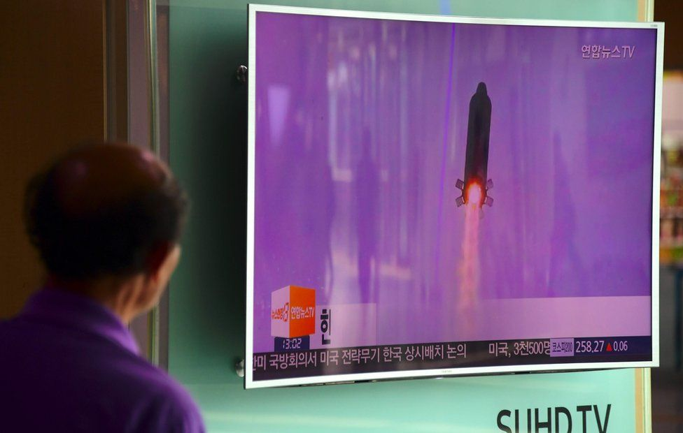 A man watches a television news report showing file footage of North Korea's missile launch at a railway station in Seoul on 20 October 2016.