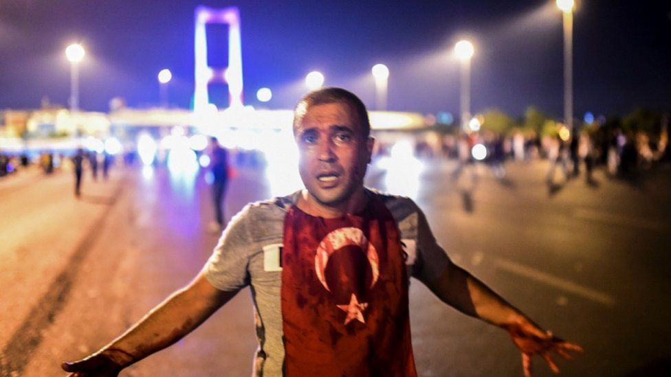 A bloodied man stands near the Bosphorus bridge in Istanbul