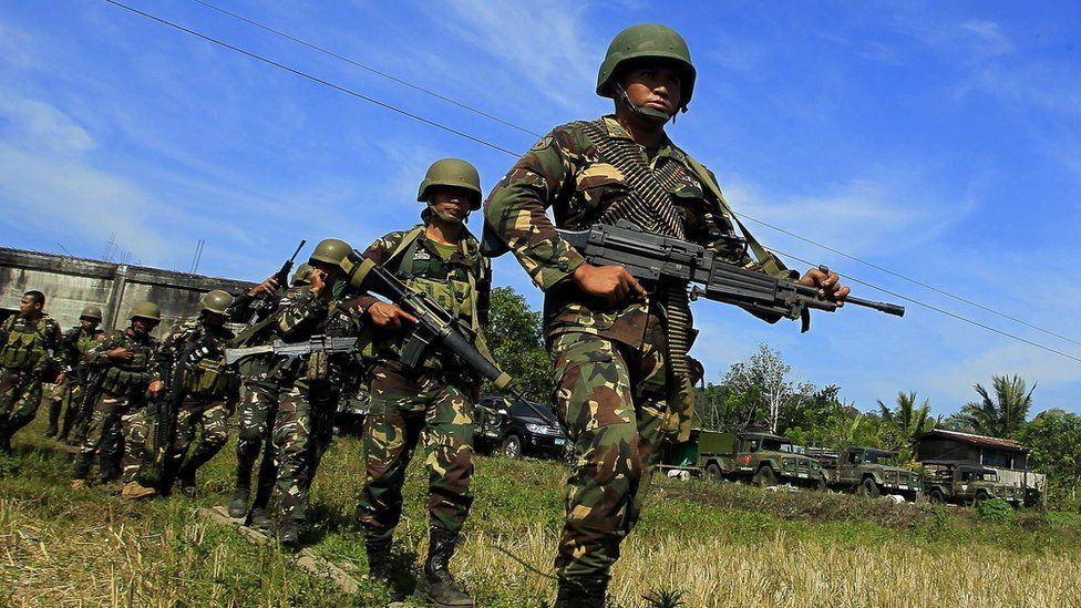 Philippine soldiers march in a rice field as they end their operation against Islamic Militants in Butig Town, Lanao Del Sur on the southern Philippine island of Mindanao
