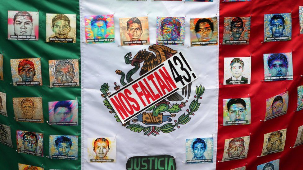 A Mexican flag and some pictures of the 43 missing students is seen in a march to demand justice for the missing students