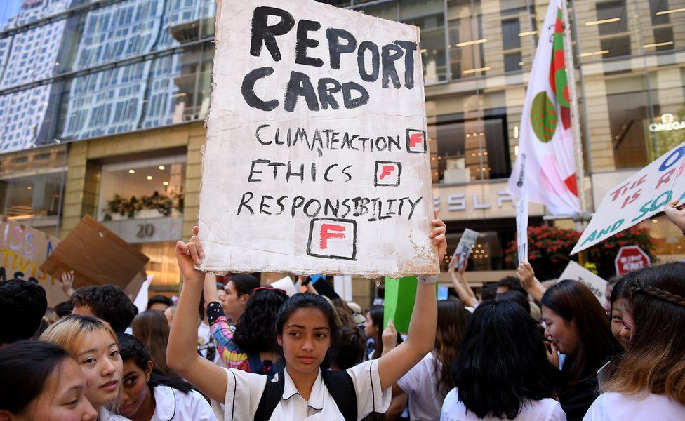 """Kayna Fichadia (C) of North Sydney Girls"""" High School holds a placard as thousands of students rally demanding action on climate change from Australian Prime Minister Scott Morrison, in Sydney, Australia, 30 November 2018."""