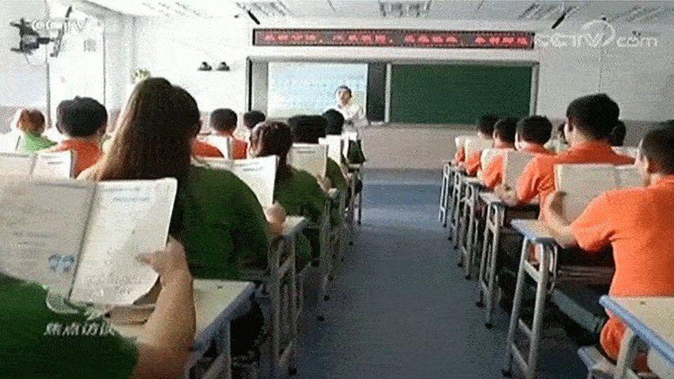 Кадр из репортажа китайского государственного телевидения об учебе в лагере