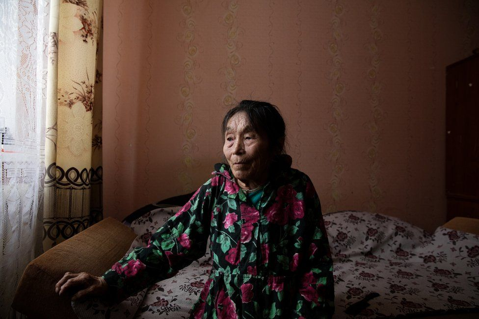 Autipana Audi (born.1941) sitting on her bed in her apartment. Yar-Sale village, Yamal Peninsula, Siberia, Russia.