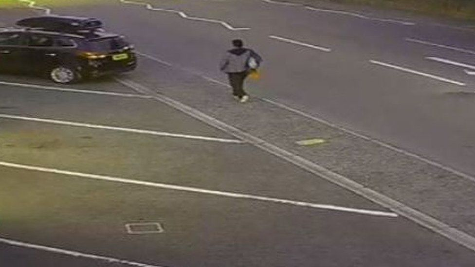 A man walking along Yarmouth Road carrying what appears to be a rucksack over one shoulder and an orange bag – possibly a Sainsbury's carrier bag