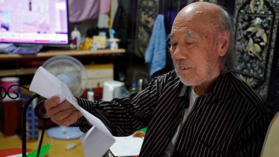 South Korean Kim Wu-jong, 87, who will travel to North Korea to meet his younger sister, looks at a document from the Red Cross during the interview at his home in Seoul, South Korea (15 October 2015)