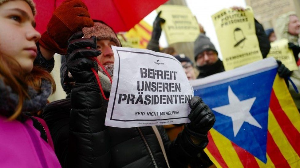 Protesters hold placards banners and flags during a demonstration in support of Catalonian ex-leader Carles Puigdemont in Berlin, Germany, 1 April 2018