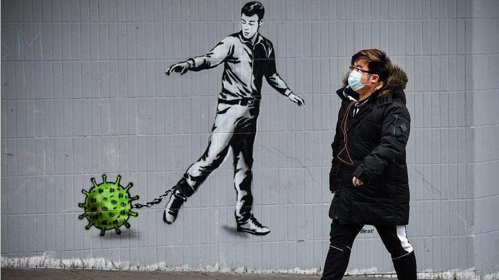 man walking past covid artwork in Glasgow