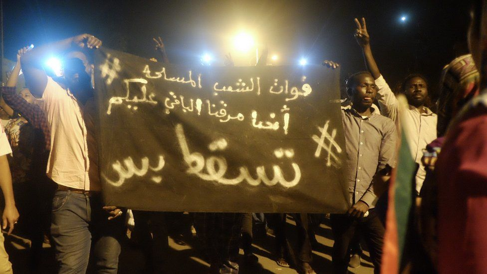 "A banner reading ""We came to protest on the street - and now it is your turn. #JustFall."" at a sit-in at the military HQ in Khartoum, Sudan - Monday 8 April 2019"