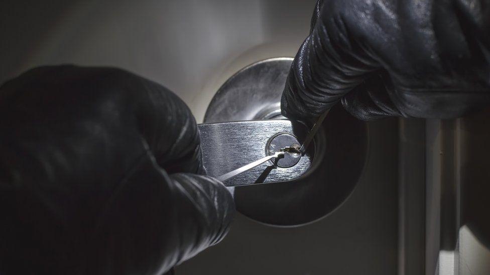 Burglar picking lock (stock image)
