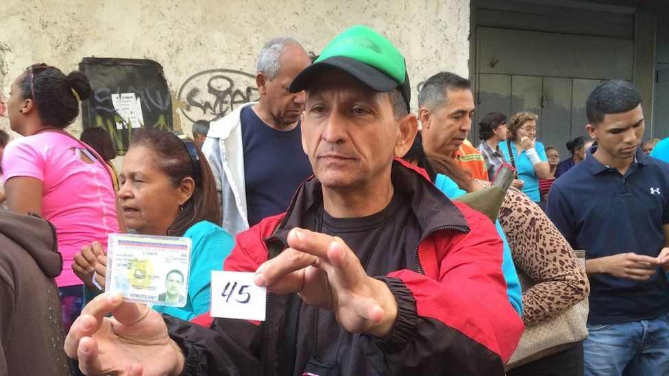 A man carries food tickets in Caracas (February 2016)