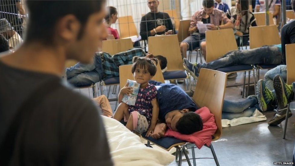 Refugees who arrived in Germany by crossing the nearby Austrian border wait in the waiting zone at the X-Point Halle initial registration centre of the German federal police (Bundespolizei) on July 15, 2015
