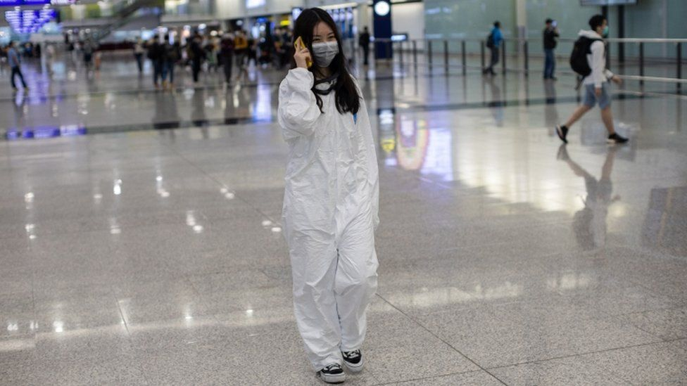 A traveller wearing a full protective gown walks into the arrival hall at Hong Kong International Airport