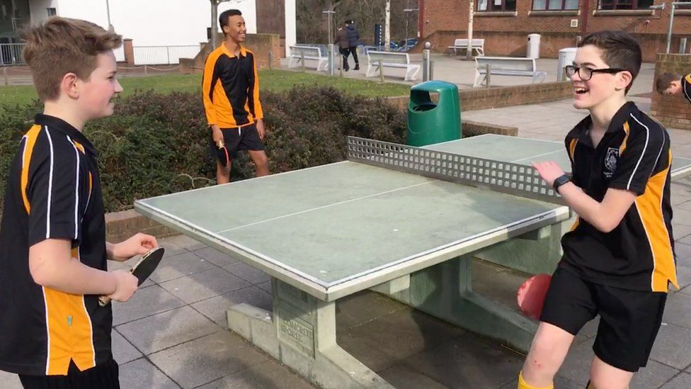 T-shirt boys playing table tennis outside in February