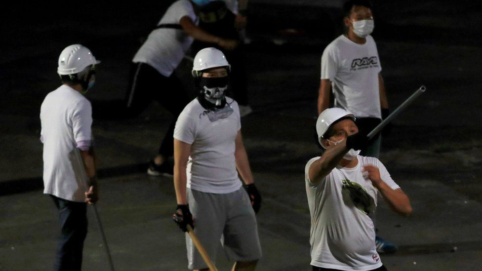 Men in white T-shirts with poles are seen in Yuen Long after attacked anti-extradition bill demonstrators at a train station, in Hong Kong