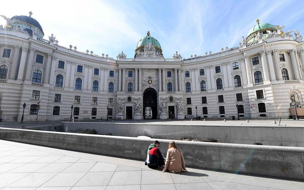 People sitting at an empty square in the centre of Vienna