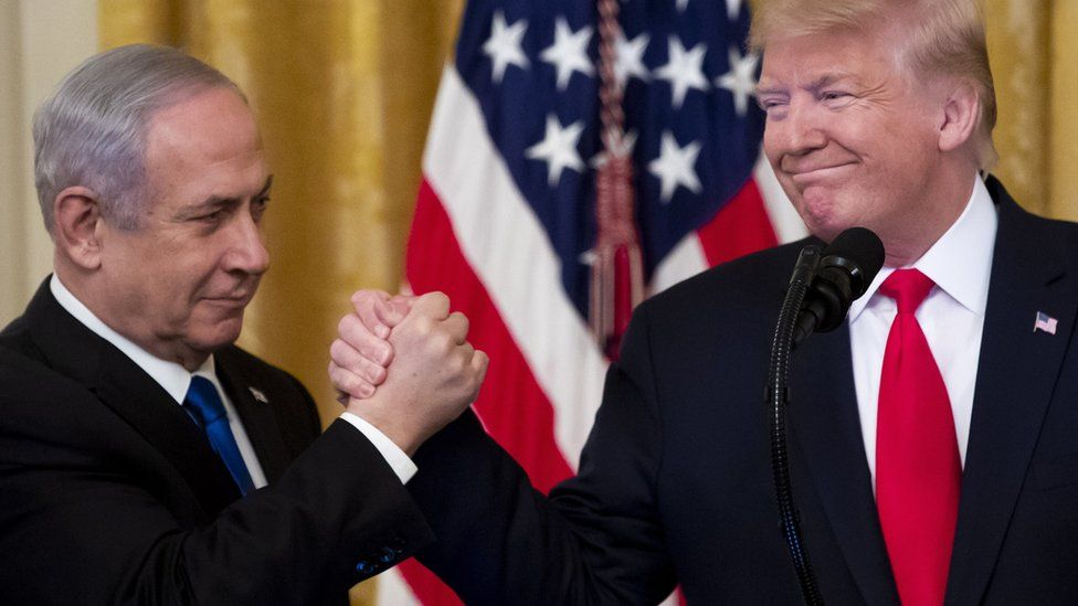 Israeli Prime Minister Benjamin Netanyahu shakes hands with Donald Trump after the unveiling of his vision for peace between Israel and the Palestinians at the White House (28 January 2020)