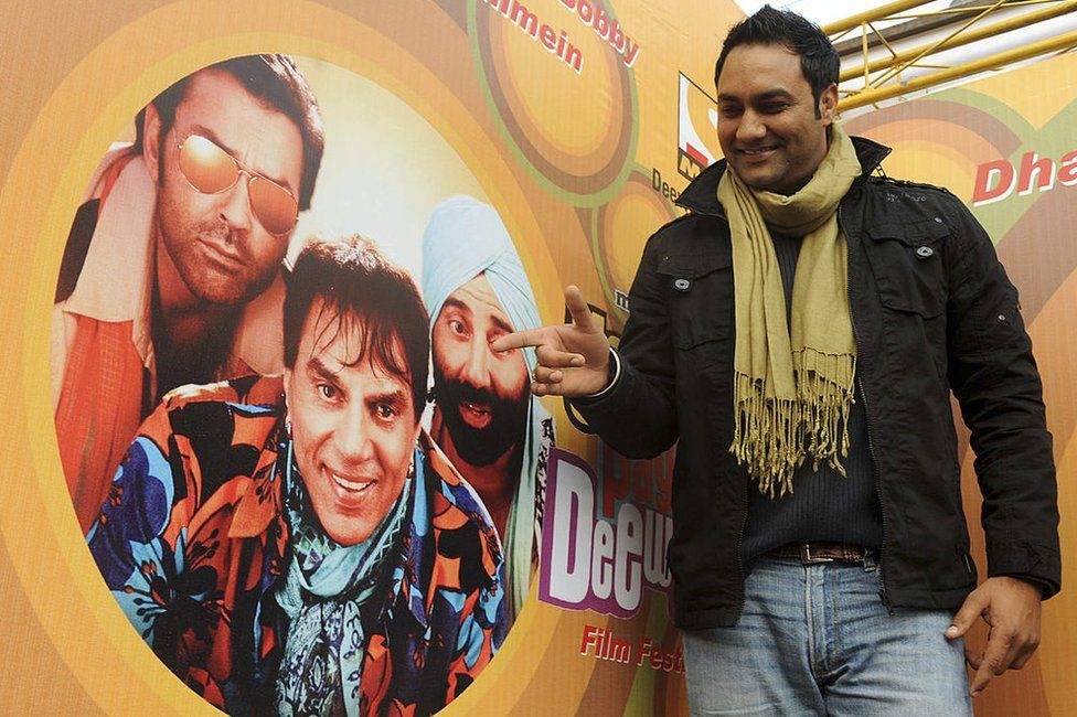 Indian Bollywood film actor and folk singer Lakhwinder Wadali poses with a poster of the new Hindi comedy film 'Yamla Pagla Deewana' during promotional roadshow event in Amritsar on January 15, 2011.