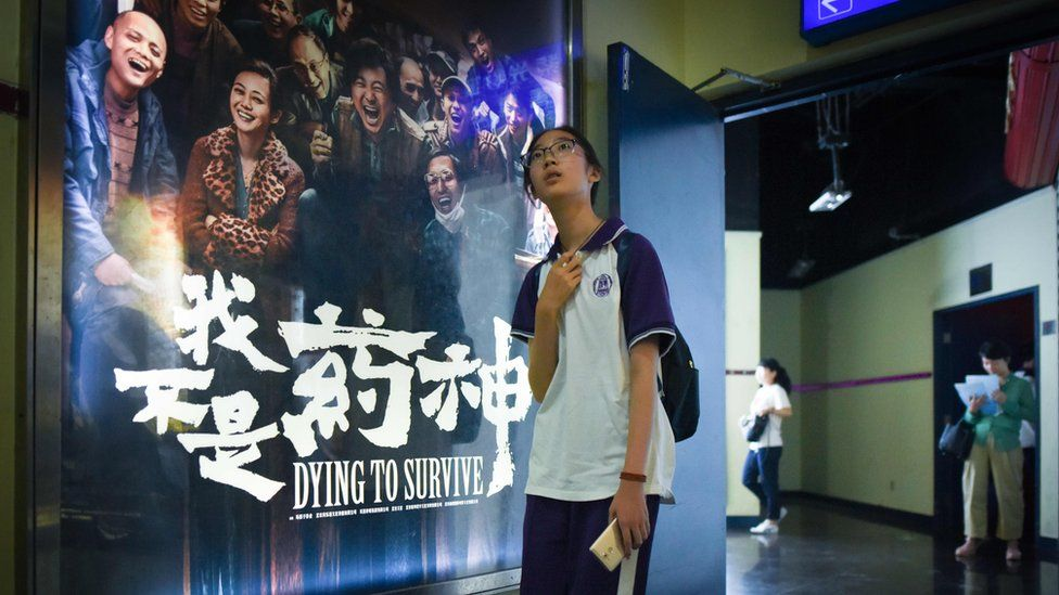 A girl walks past a poster of the film Dying to Survive at a cinema in Beijing, 12 July