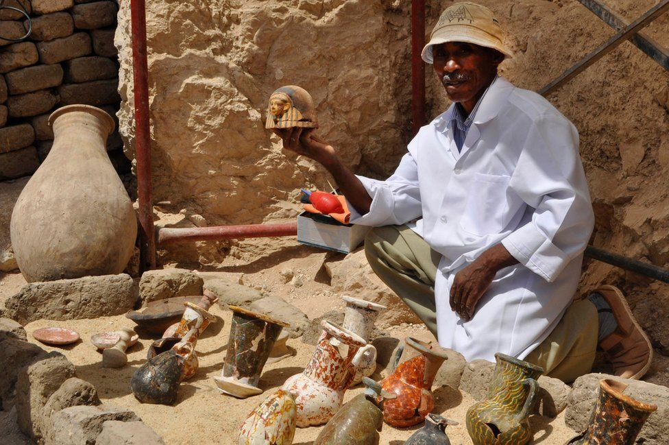 man holding pottery surrounded by jugs