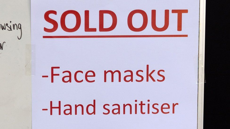 Sign in shop window saying that face masks and hand sanitiser have sold out