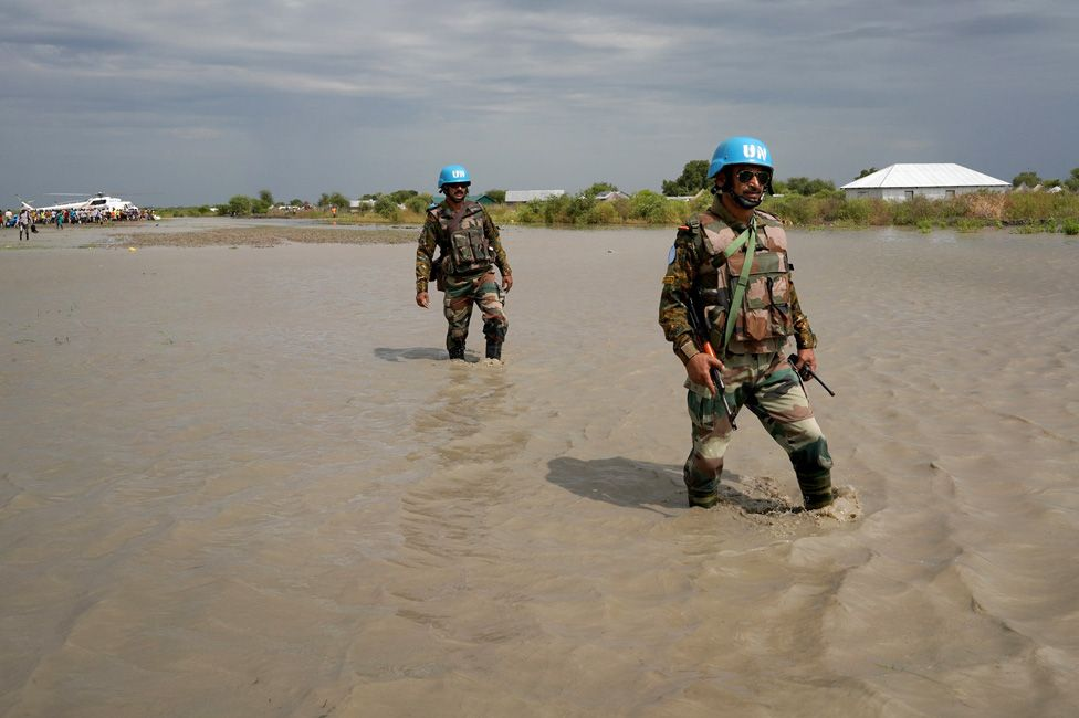 UN peacekeepers walk through water, after heavy rains and floods forced hundreds of thousands of people to leave their homes, in the town of Pibor