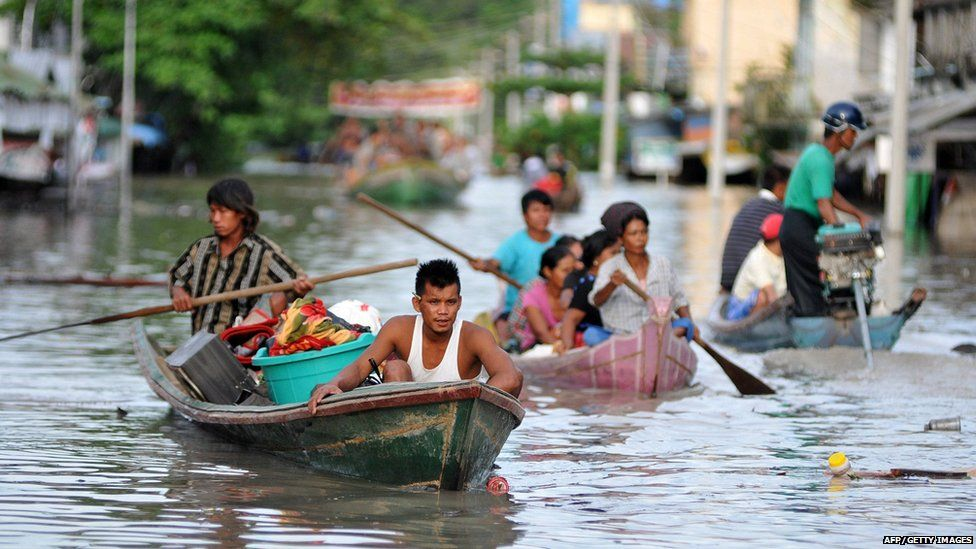 Resident paddle through floodwater in Kalay, Sagaing Region, Upper Myanmar on August 1, 2015.