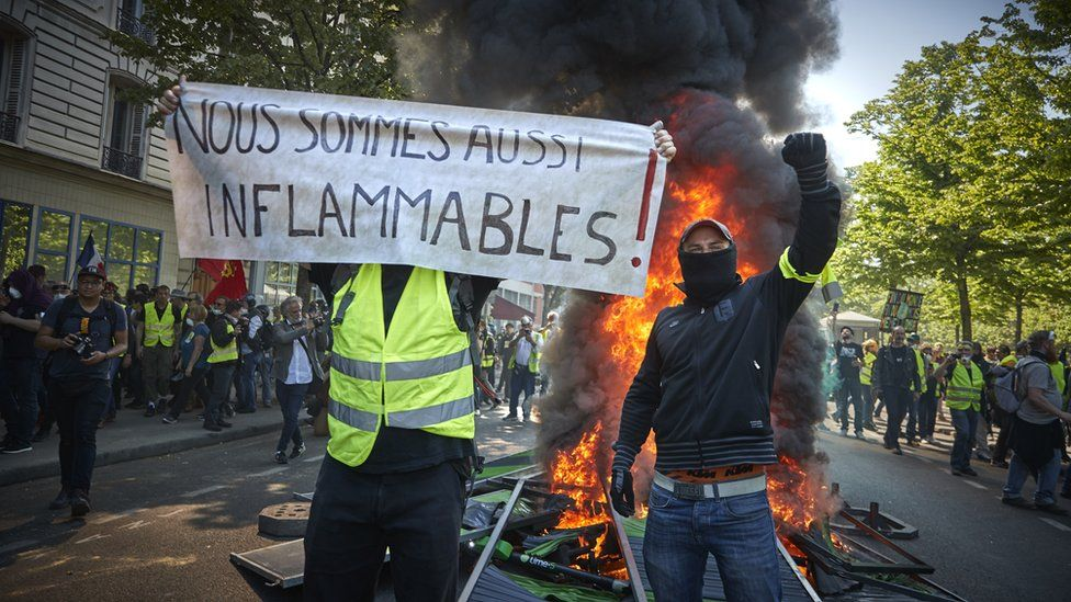 Gilets jaunes (yellow-vests) are seen standing in front of a burning barricade with a banner reading 'we can also burn' on 20 April
