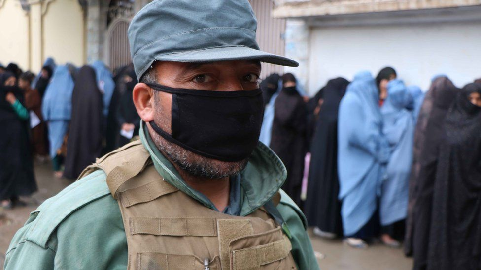 Security force stands guard as women line up to receive free ration distributed by WFP