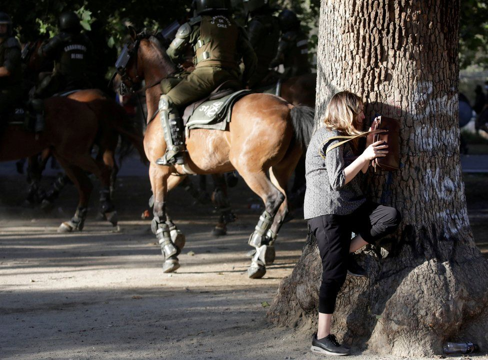A woman takes cover behind a tree during clashes