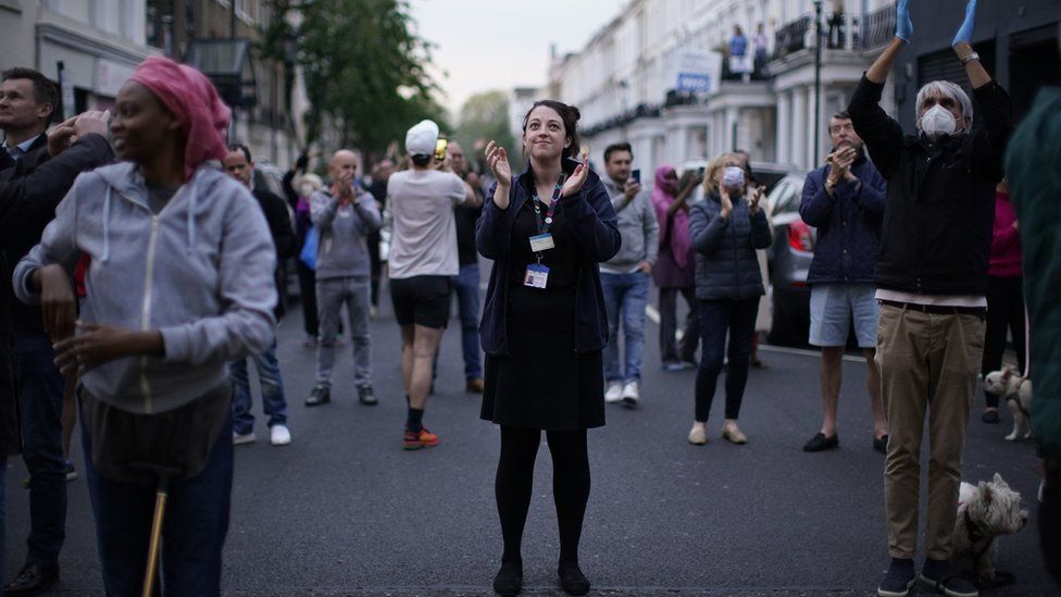 People gather on the street to clap for the NHS