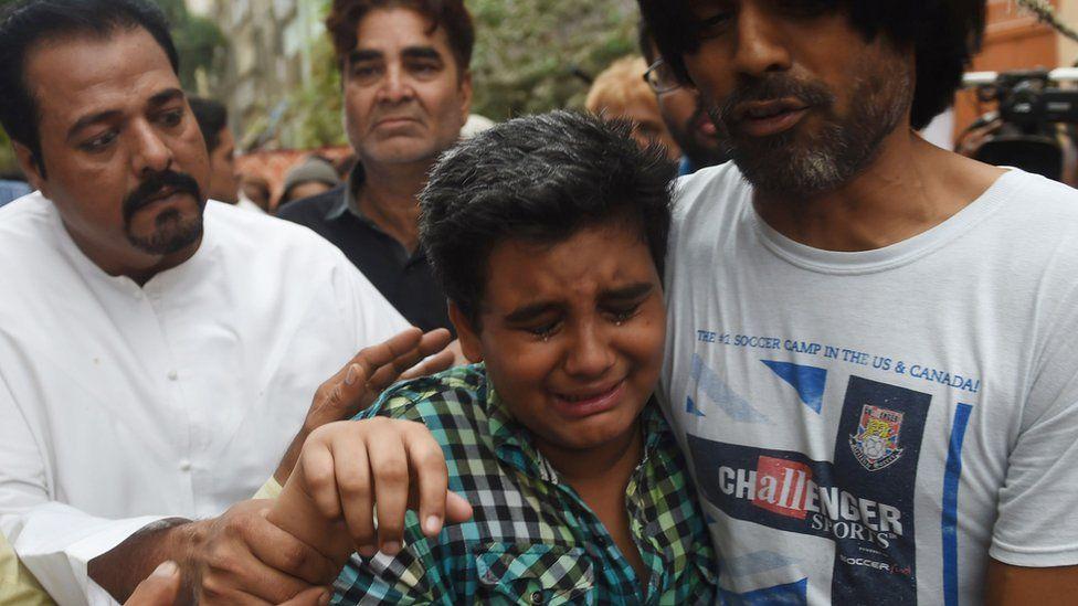 Pakistani relatives comfort Mujjudid Sabri (C), the son of Pakistani Sufi musician Amjad Sabri, who was killed in an attack by unknown gunmen in Karachi on 22 June 2016.
