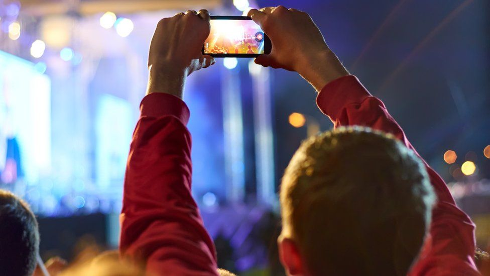 Man videoing concert on mobile phone