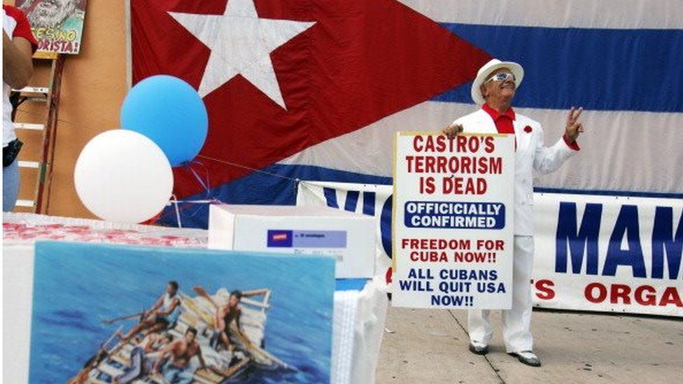 An anti-Castro protester flashes a victory sign as he stands in front of a Cuban flag (rear) and near a booth promoting human rights in Cuba (bottom left) during a small anti-Castro rally in Miami, Florida 08 November 2006.