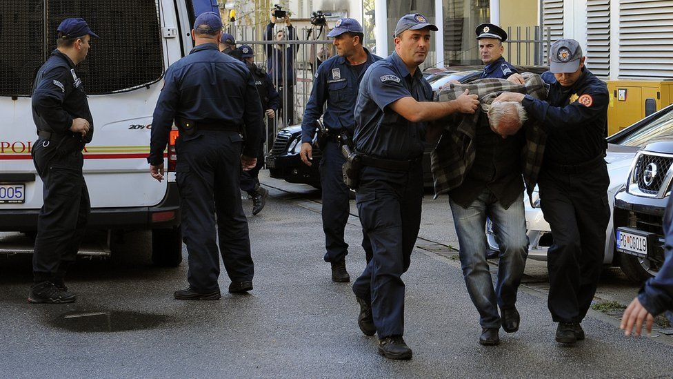A man is escorted by Montenegrin police officers to the special court in Podgorica on October 16, 2016