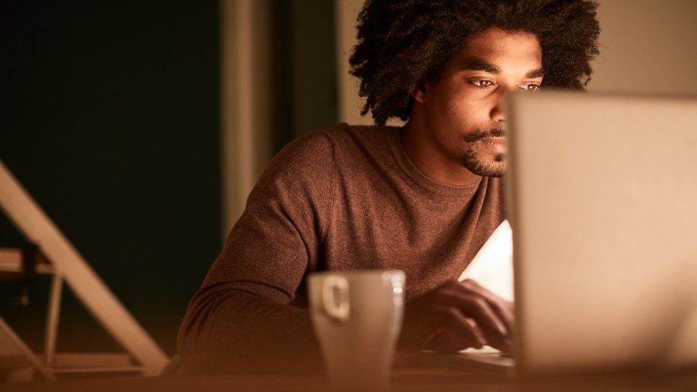 Man behind computer considering finances