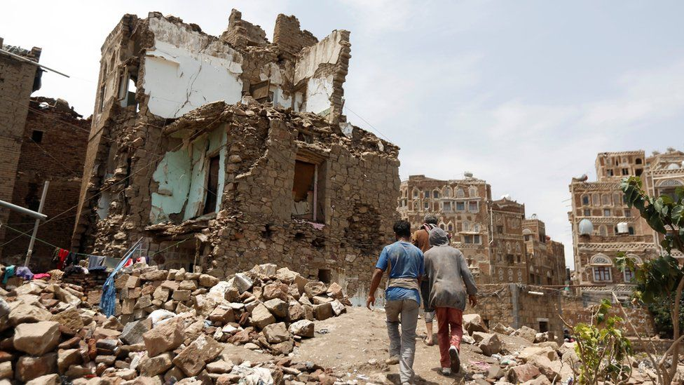 People walk past a house destroyed by an air strike in the Old City of Sanaa, Yemen (8 August 2018)