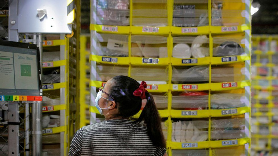 "An employee fills a cart full of items at Amazon""s JFK8 distribution center in Staten Island, New York, U.S. November 25, 20"