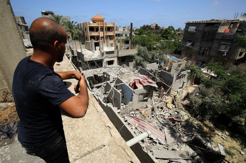 A man looks at the debris of a building in Khan Yunis, Gaza, on May 20, 2021